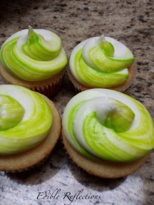 Vanilla cupcakes with a swirl of neon green food coloring in the buttercream