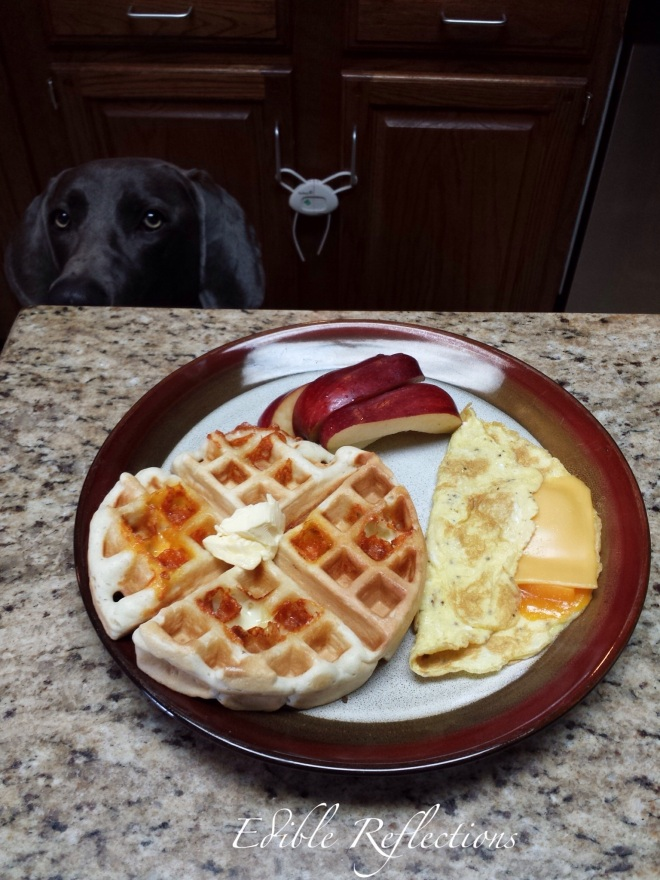Homemade waffle, scrambled eggs and apple slices