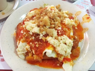 Centenario Breakfast: 2 fried eggs over 'hojaldra', ground 'chicharron', shredded white cheese and y salsa.